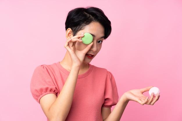 Jonge aziatische vrouw die kleurrijke franse macarons houdt