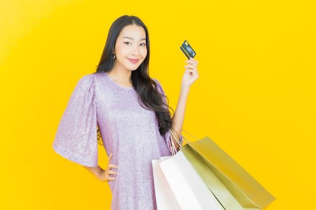 Jonge aziatische vrouw die lacht met boodschappentas op geel