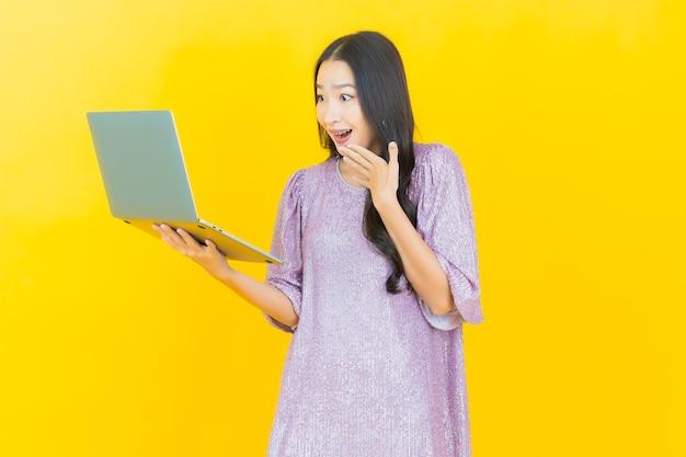 Jonge aziatische vrouw die lacht met computer laptop