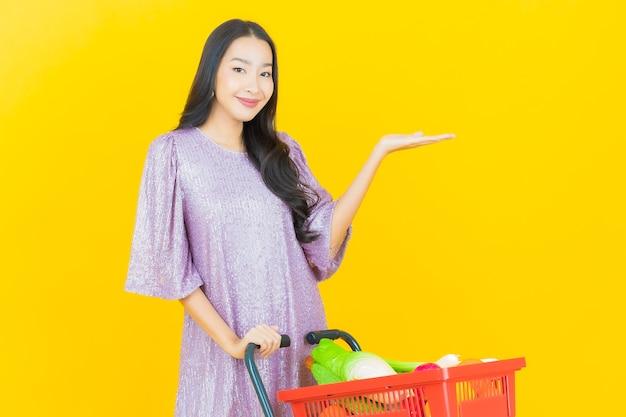 Jonge aziatische vrouw die lacht met een boodschappenmand van de supermarkt op geel