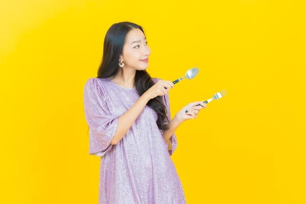 Jonge aziatische vrouw die lacht met lepel en vork op geel
