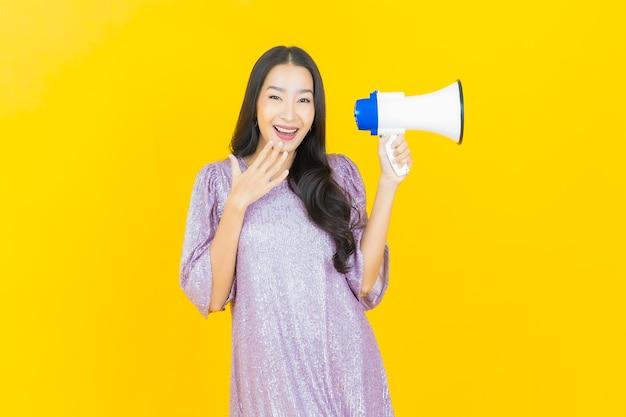 Jonge aziatische vrouw die lacht met megafoon op geel