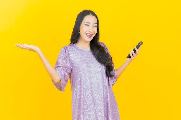 Jonge aziatische vrouw die lacht met slimme mobiele telefoon op geel