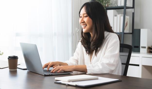 Jonge aziatische vrouw die laptop gebruikt met creatief werken op kantoor aan huis.