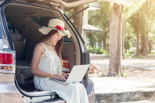 Jonge aziatische vrouw die laptop in kledingszitting met behulp van in auto, meisje freelancer het werken