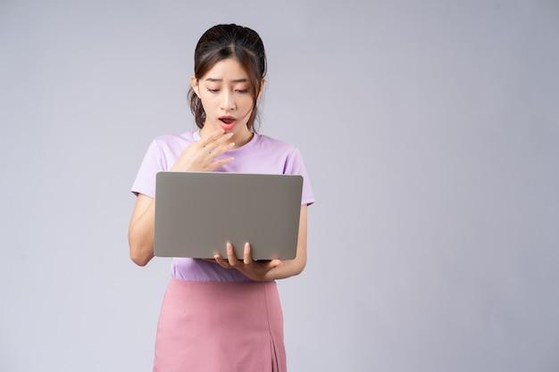 Jonge aziatische vrouw die laptop op grijs met behulp van