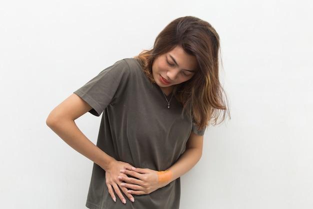Jonge aziatische vrouw die lijdt aan lage rugpijn en lumbale pijn in de taille