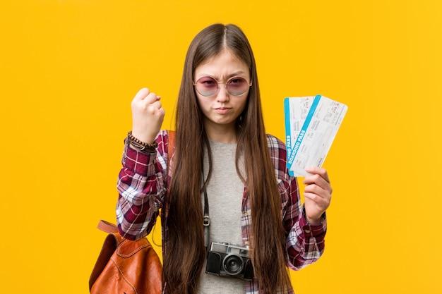Jonge aziatische vrouw die luchtkaartjes houden die vuist tonen aan met agressieve gelaatsuitdrukking.