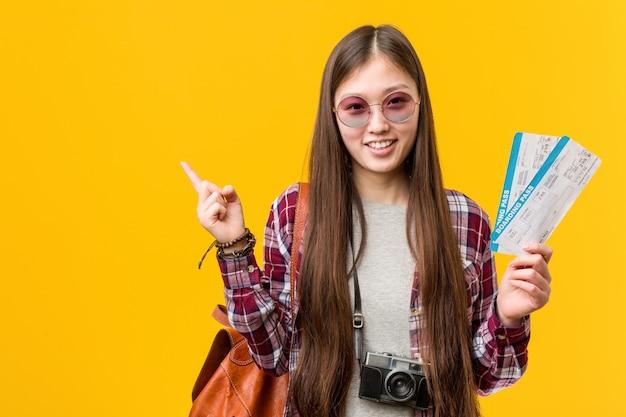 Jonge aziatische vrouw die luchtkaartjes houden glimlachend vrolijk wijzend met weg wijsvinger.