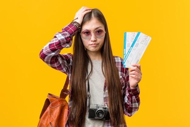 Jonge aziatische vrouw die luchtkaartjes houdt die worden geschokt, heeft zij belangrijke vergadering herinnerd.