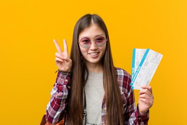 Jonge aziatische vrouw die luchtkaartjes tonen die overwinningsteken tonen en breed glimlachen