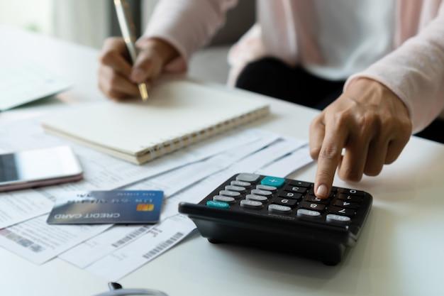 Jonge aziatische vrouw die maandelijkse kosten berekenen bij haar bureau. home opslaan concept. financieel en termijn betaling concept. detailopname.