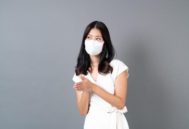 Jonge aziatische vrouw die masker draagt ter bescherming van coronavirus (covid-19)
