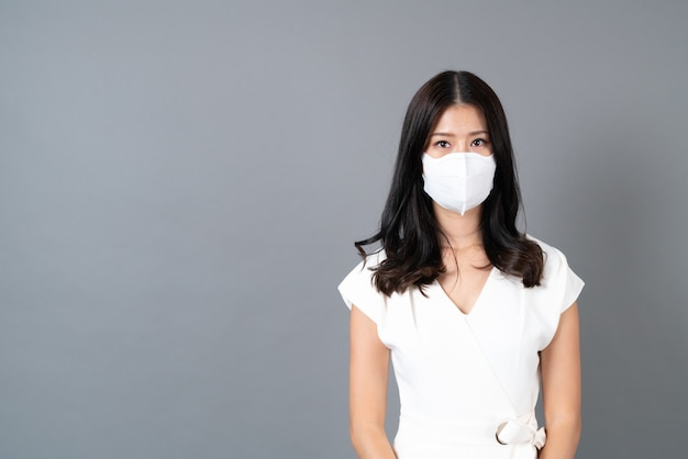 Jonge aziatische vrouw die masker draagt ter bescherming van het coronavirus (covid-19)