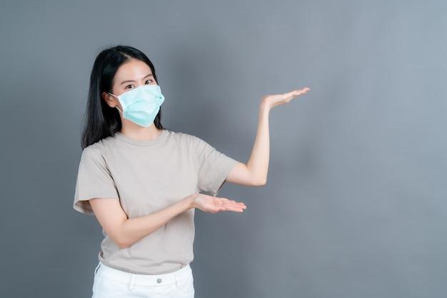 Jonge aziatische vrouw die medisch gezichtsmasker draagt, beschermt filterstof pm2