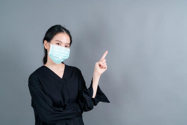 Jonge aziatische vrouw die medisch gezichtsmasker en vinger dragen die op exemplaarruimte richten