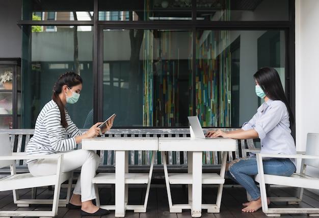 Jonge aziatische vrouw die medisch masker in sociale distantiërende zitting draagt die aan laptop thuis bureau werkt
