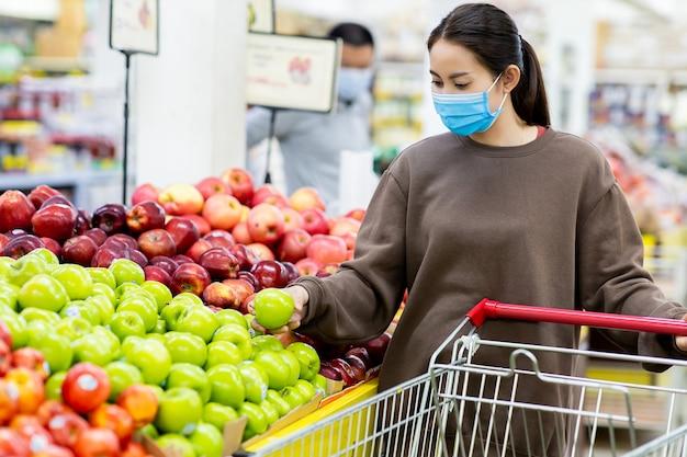 Jonge aziatische vrouw die met beschermend masker boodschappenwagentje duwt voor het kopen van vers fruit in supermarkt tijdens virus covid-19-uitbraak. concept ter preventie van covid-19 virus.