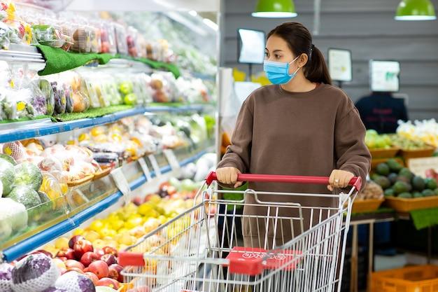 Jonge aziatische vrouw die met beschermend masker boodschappenwagentje duwt voor het kopen van verse groenten in supermarkt tijdens uitbraak van virus covid-19.