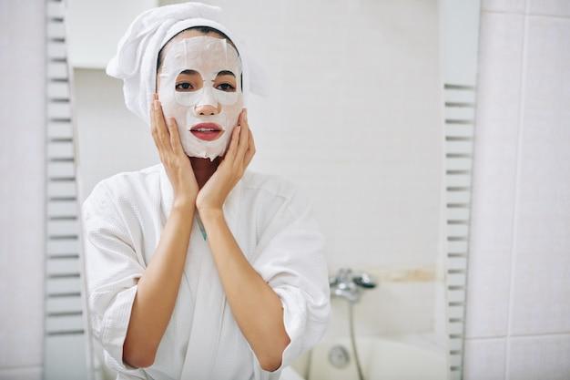 Jonge aziatische vrouw die met bladmasker op haar gezicht in spiegel kijkt