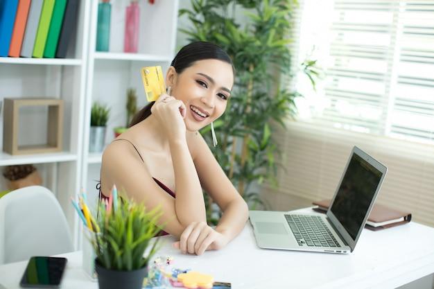 Jonge aziatische vrouw die met creditcard betaalt