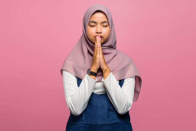 Jonge aziatische vrouw die met gevouwen hand bidt