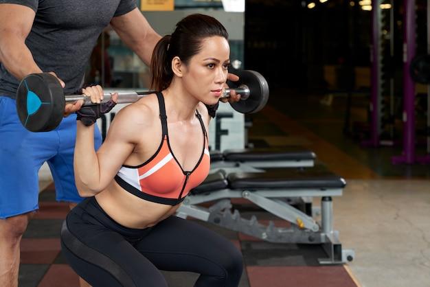 Jonge aziatische vrouw die met gewicht uitoefent dat door haar persoonlijke instructeur wordt gesteund