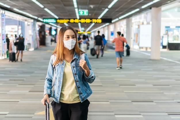 Jonge aziatische vrouw die met gezichtsmasker bij luchthaventerminal loopt. gezondheidszorg en bescherming concept.