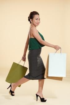 Jonge aziatische vrouw die met het winkelen zakken loopt