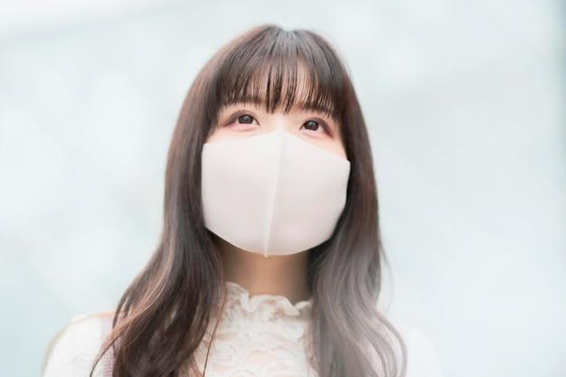 Jonge aziatische vrouw die met lang haar uitgaat dat een masker draagt