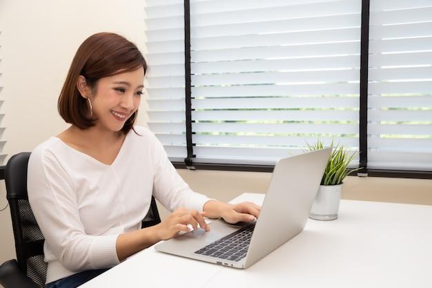 Jonge aziatische vrouw die met laptop computer aan wit bureau bij haar flat werken, het werk van huisconcept