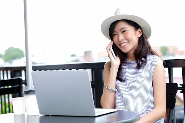 Jonge aziatische vrouw die met laptop computer en sprekende telefoon bij de achtergrond van het aardpark werken