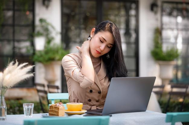 Jonge aziatische vrouw die met laptop computer in tuin werkt en halspijn heeft
