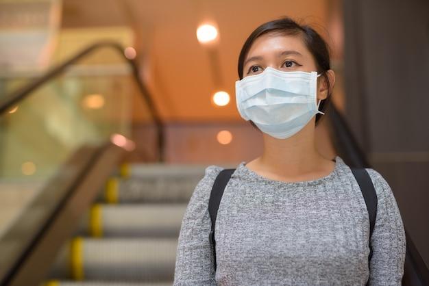 Jonge aziatische vrouw die met masker denkt voor bescherming tegen uitbraak van het coronavirus die de roltrap afdaalt