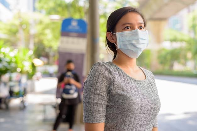 Jonge aziatische vrouw die met masker wacht op bescherming tegen de uitbraak van het coronavirus bij de bushalte