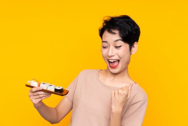 Jonge aziatische vrouw die met sushi een overwinning viert