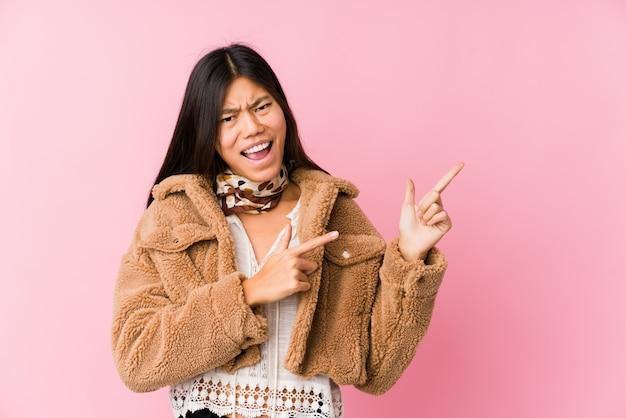 Jonge aziatische vrouw die met wijsvingers aan een exemplaarruimte richt, opwinding en wens uitdrukt.