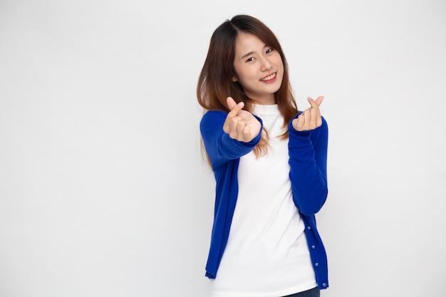 Jonge aziatische vrouw die minihartteken toont dat op witte muur wordt geïsoleerd.
