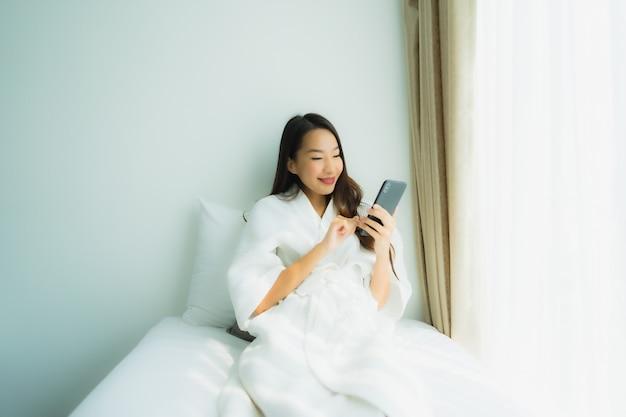 Jonge aziatische vrouw die mobiele slimme telefoon op bed met behulp van
