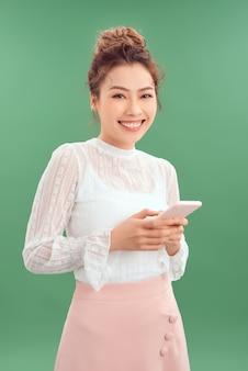 Jonge aziatische vrouw die mobiele telefoon gebruikt terwijl ze geïsoleerd staat over groene achtergrond.