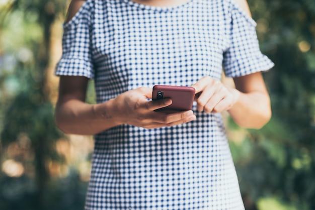 Jonge aziatische vrouw die mobiele telefoon openluchtaard gebruiken