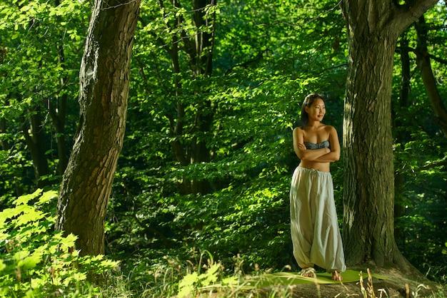 Jonge aziatische vrouw die na yoga in het bos rust