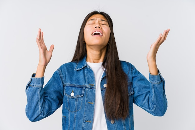 Jonge aziatische vrouw die naar de hemel gilt, omhoog kijkt, gefrustreerd.