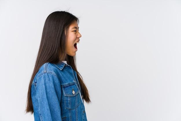 Jonge aziatische vrouw die naar een exemplaarruimte schreeuwt