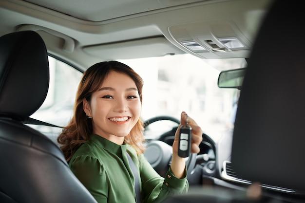 Jonge aziatische vrouw die nieuwe auto koopt