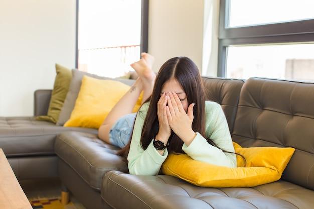 Jonge aziatische vrouw die ogen bedekt met handen met een droevige, gefrustreerde blik van wanhoop, huilend, zijaanzicht