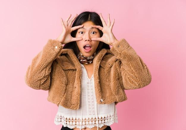 Jonge aziatische vrouw die ogen houdt geopend om een succeskans te vinden.