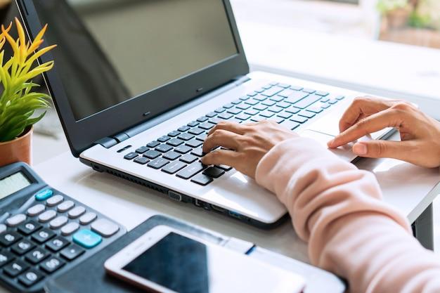 Jonge aziatische vrouw die online met computerlaptop thuis werken terwijl het zitten op de bank. detailopname.