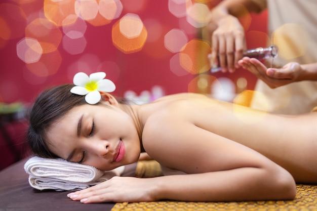 Jonge aziatische vrouw die op bed in kuuroordmassage ligt.