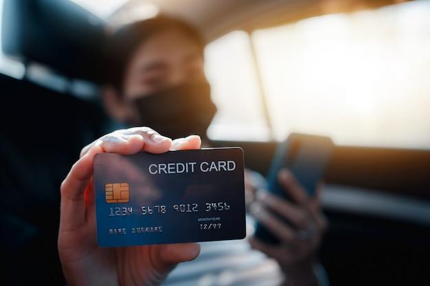 Jonge aziatische vrouw die op de achterbank van de auto zit en mobiel gebruikt en creditcard in handen houdt.